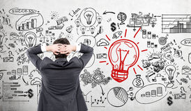 Businessman looking at startup icons and red light bulb sketch Stock Photos