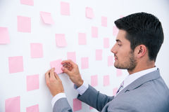 Businessman looking at sticker on wall Royalty Free Stock Photos