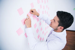 Businessman looking at sticker on wall Stock Image