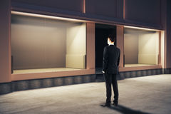 Businessman looking at storefront. Confident businessman looking at empty clean storefront at night. Side view, Mock up, 3D Rendering Royalty Free Stock Photo