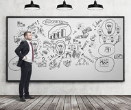 Businessman looking at successful business icons Stock Image
