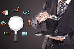 Businessman looking at tablet with magnifying glass. Icons of analysis Stock Photos