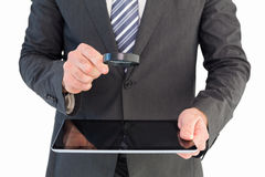 Businessman looking at tablet with magnifying glass Royalty Free Stock Photo