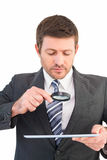 Businessman looking at tablet with magnifying glass Royalty Free Stock Images