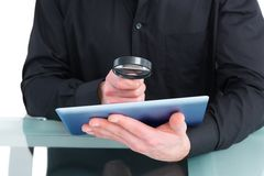 Businessman looking at tablet with magnifying glass stock photo