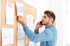 Businessman looking at task board and talking on the phone Stock Photos