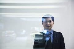 Businessman looking thorough window in parking garage Stock Image
