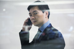 Businessman looking thorough window in parking garage, reflection of car royalty free stock images
