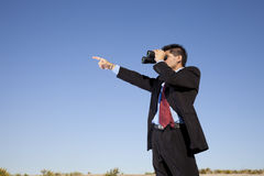 Businessman looking though binoculars Stock Photo