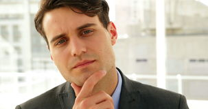 Businessman looking thoughtfully at camera