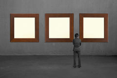 Businessman looking at three blank wooden frames on concrete wal Royalty Free Stock Photos