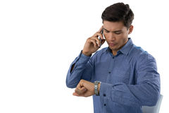 Businessman looking time while talking on smartphone Stock Photo