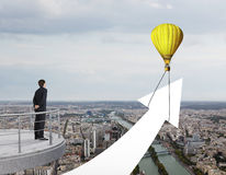 Businessman looking to baloon. With arrow Stock Photo