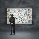 Businessman looking to blackboard Stock Images