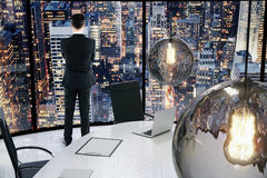 Businessman looking to the city at evening in a conference room Stock Images