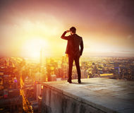 Businessman looking to the future for new business opportunity. Businessman looks at the city during sunset. Future and new business opportunity concept Stock Images