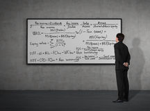 Businessman looking to mathematic formulas Stock Photo