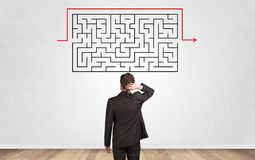 Businessman looking to a maze on a wall royalty free stock photo