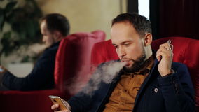 Businessman looking to the phone and smoking electronic cigarette stock footage