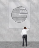 Businessman looking to pie chart. On white placard Stock Image