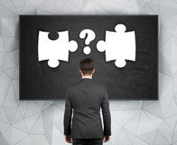 Businessman looking to puzzle. And question mark drawing on blackboard Stock Photography