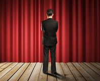Businessman looking to red curtains Stock Image