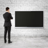Businessman looking  to TV Stock Image