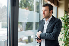 Businessman is looking trough the window Royalty Free Stock Image