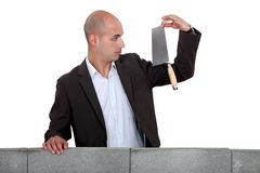 Businessman looking at a trowel. Royalty Free Stock Photography