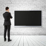 Businessman looking  TV. Businessman looking  to wide screen TV on brick wall Royalty Free Stock Image