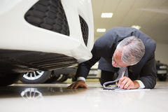 Businessman looking under the car while writing on clipboard Royalty Free Stock Photography