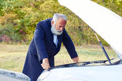 Businessman looking under the hood of breakdown car. Senior businessman looking under the hood of breakdown car at outdoor Stock Image