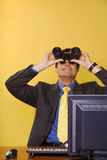 Businessman looking up. Business vision: businessman looking up though binoculars Royalty Free Stock Image