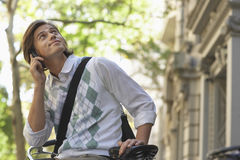 Businessman Looking Up While Answering Phone Call On Bicycle Stock Image
