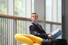 Businessman looking up with blue folder in her hand Royalty Free Stock Photography