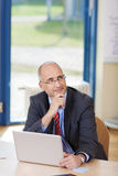 Businessman Looking Up At Desk Stock Photo