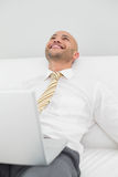 Businessman looking up while using laptop. Smiling elegant young businessman looking up while using laptop on sofa at home Stock Photos