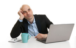 Businessman looking up while working at laptop Stock Photo