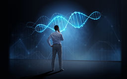 Businessman looking at virtual dna molecule. Business, people, technology and science concept - businessman looking at virtual dna molecule projection over dark royalty free stock images