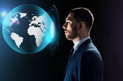 Businessman looking at virtual earth projection Royalty Free Stock Images