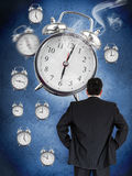 Businessman looking at wall of alarm clocks Stock Images