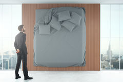 Businessman looking at wall with bed Royalty Free Stock Photography