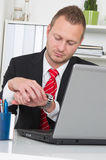 Businessman looking at watch with laptop - end of work Stock Photography