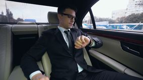 Businessman looking at watch late for meeting stuck in traffic jam in luxury car. Stock footage stock video footage