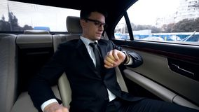Businessman looking at watch late for meeting stuck in traffic jam in luxury car royalty free stock image
