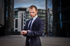 Businessman looking at watches. While walking outside modern office building Stock Images