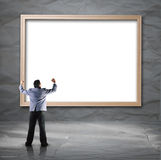 Businessman looking for white backdrop with wooden frame Stock Photo