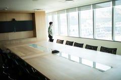 Businessman looking through window in meeting room Stock Photos