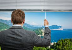 Businessman is looking through the window with sea Stock Photos