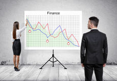 Businessman looking at woman, giving presentation on tablet with finance graphs Stock Photo